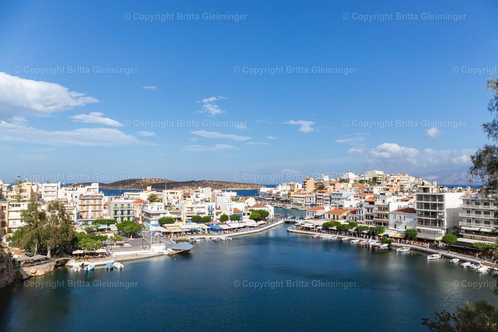 Panorama-Ansicht von Agios Nikolaos | Agios Nikolaos ist eine Küstenstadt im Nordosten der Insel Kreta in Griechenland. Sie besticht durch ihr mediterranes Flair, die Freundlichkeit der Einwohner und ihrer unfassbaren Schönheit. Vom Hafen gelangt man durch einen schmalen Kanal zum Binnenhafen, in dem Fischerboote und kleine Yachten beieinander liegen. Anders als bei anderen Häfen, ist das Wasser in Agios Nikolaos glasklar und tief-türkis.