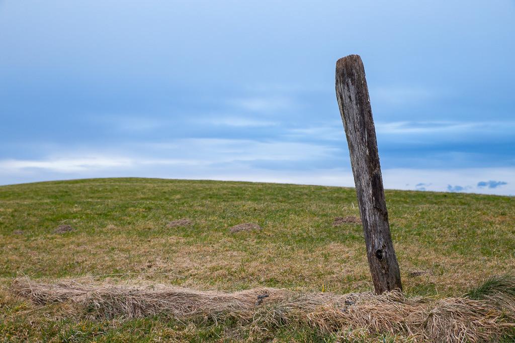 Einsam | Fast wie einsam steht er da, dieser Pfosten auf der Wiese in der Nähe vom Irschenberg.