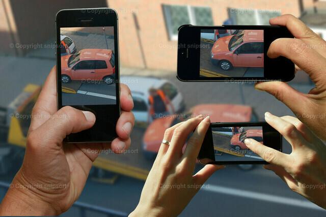 Gaffer filmen ein Auto beim Abschleppen | Neugierige Gaffer filmen mit den Smartphones ein Auto beim Abschleppen