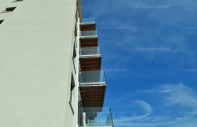 Urlaub auf Balkonien | Hochhausfassade mit Balkonen mit blauem Himmel im Hintergrund.