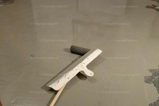 Bodenausgleichsmasse | Detail von einer Stachelrolle und einem Flächenrakel mit ausgekippter Bodennivelliermasse