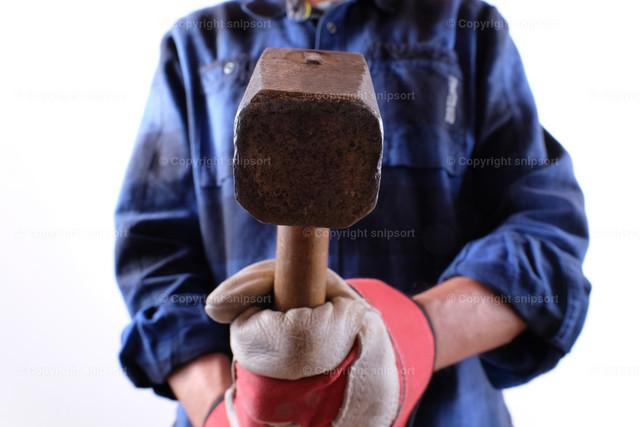 Arbeitender Handwerker mit einem schweren Hammer | Konzept eines arbeitenden Handwerkers.