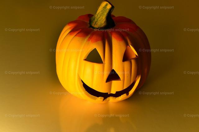 Halloweenkürbis | Ein gelber Halloweenkürbis auf einem gelben, spiegelnden Untergrund.
