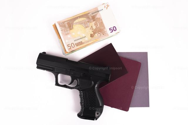Pistole auf Reisepässen und einem Geldstapel | Konzept einer illegalen Tätigkeit mit einer Pistole und Geldscheinen.
