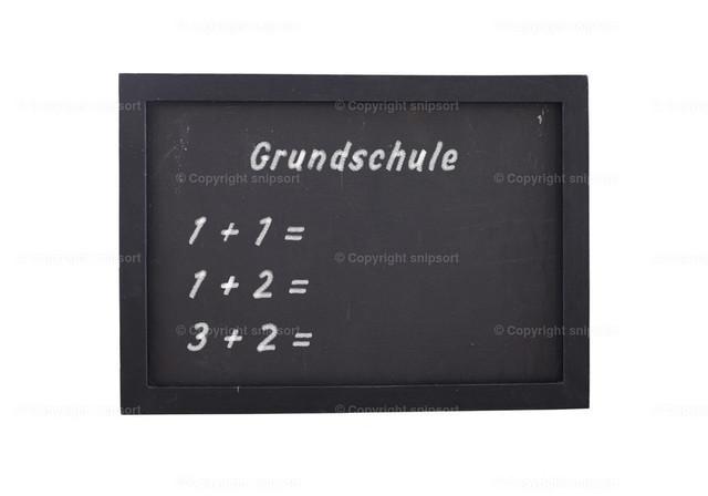 Aufgemalte Grundschulrechenaufgaben auf einer schwarzen Tafel | Eine Schultafel vor weißem Hintergrund mit mit Kreide aufgeschriebenen Aufgaben für die Grundschule.