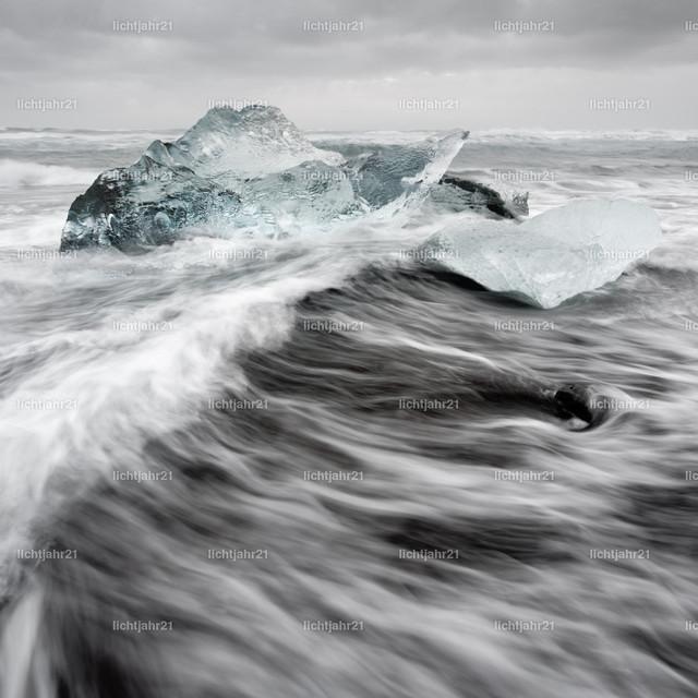 Eisblöcke in der Brandung | Eisblöcke an einem Strand mit starker Brandung, die Dynamik einer Welle ist zu sehen (Langzeitbelichtung, Bewegungsspuren), darüber ein bewölkter Himmel - Location: Island, Jökulsarlon (Jökulsárlón)