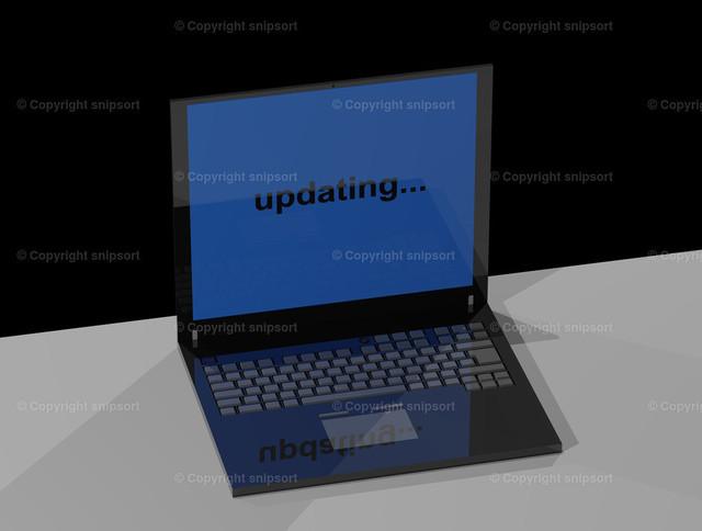 Laptop mit Meldung updating... | Ein Notebook auf dem Tisch mit der Meldung