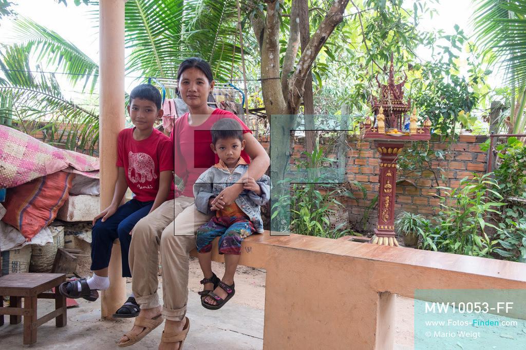 MW10053-FF | Kambodscha | Siem Reap | Reportage: Sombath erkundet Angkor | Sombath mit seiner Mutter Theavy und jüngeren Bruder Toric zu Hause. Der achtjährige Sombath lebt in Kambodscha im Dorf Anjan, sechs Kilometer westlich von Siem Reap entfernt. In seiner Freizeit nimmt ihn manchmal sein Onkel in die berühmte Tempelanlage von Angkor mit. Besonders mag er die riesigen Wurzeln der Kapokbäume, die auf den uralten Mauern wachsen. Seine Lieblingstempel in Angkor sind Ta Prohm, Banteay Kdei und Preah Khan.  ** Feindaten bitte anfragen bei Mario Weigt Photography, info@asia-stories.com **
