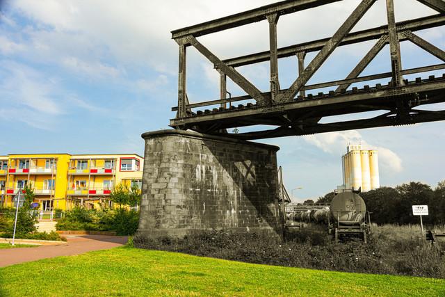 Eisenbahnbrücke aus Stahl endet in Wohnsiedlung | Eisenbahnbrücke aus Stahl endet abrupt in einer Wohnsiedlung. In Schwarzweiß und Farbe. Es stehen Chemiewaggons vor einem Silo im Hintergrund.