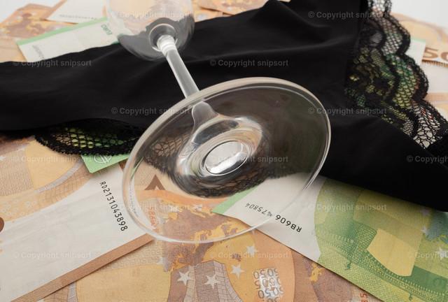 Konzept Escortservice | Ein schwarzes Damenhöschen auf Eurobanknoten mit einem umgekippten Glas Sekt