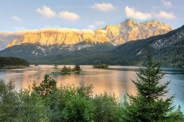 Eibsee am Abend | Blick über den Eibsee in Richtung Wettersteingebirge mit der Zugspitze als höchsten Gipfel. Kurz vor Sonnenuntergang wird die Bergkette in ein schönes warmes Licht getaucht, das auch als Alpenglühen bezeichnet wird.