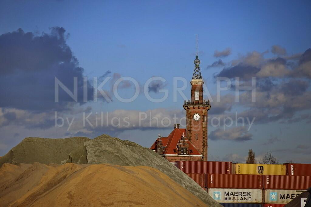 Altes Hafenamt Dortmund | Der Turm des alten Hafenamtes in Dortmund vor der Kulisse des Hafens. Die aufgeschütteten Baustoffe sowie die Container geben einen Eindruck von der Logistik des Hafens, der den Endpunkt des Dortmund-Ems-Kanals darstellt. Das Gebäude wurde bis zum Jahr 1962 für die Hafenverwaltung genutzt. Mit einer Höhe von 38m ist der markante Turm des alten Hafenamtes bereits von weitem gut sichtbar.