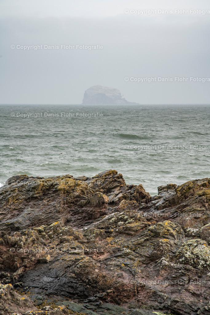 Insel in der Brandung #2 | Eine Insel in der Brandung, im Vordergrund ein Stück Fels welches dank der Ebbe zu sehen ist.