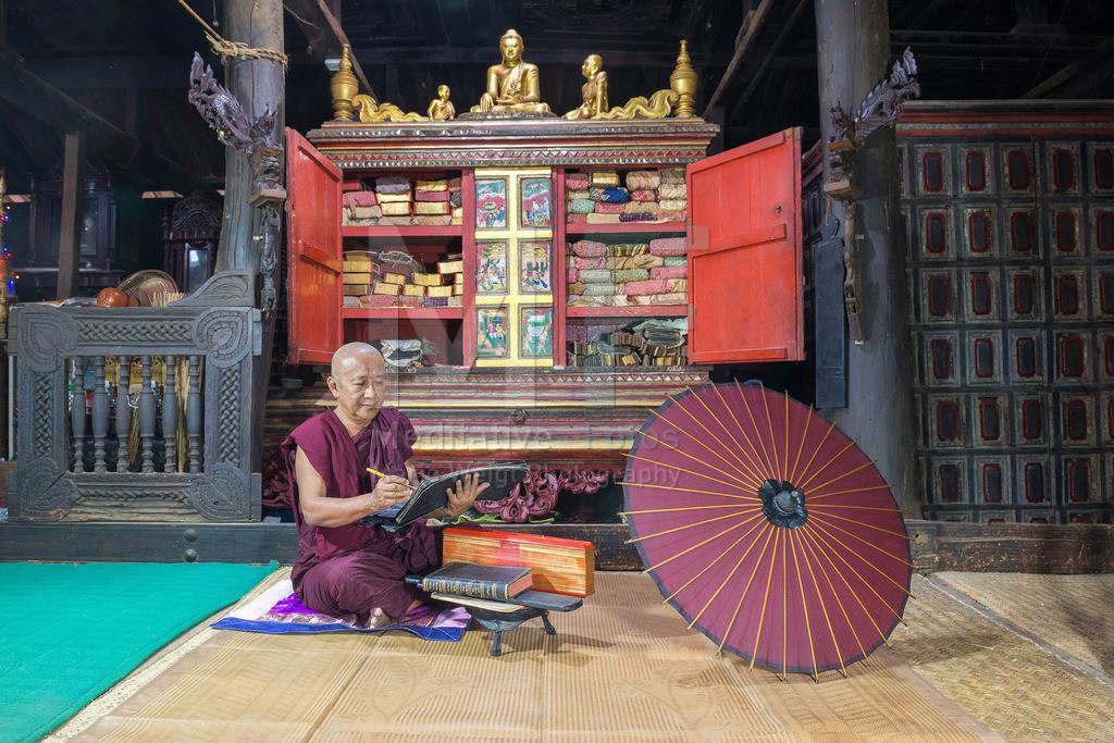 MW1119-2719 | Fotoserie DER ROTE SCHIRM | Ein Mönch rezitiert Pali-Schriften vor einer Palmblatt-Bibliothek in seinem buddhistischen Kloster.