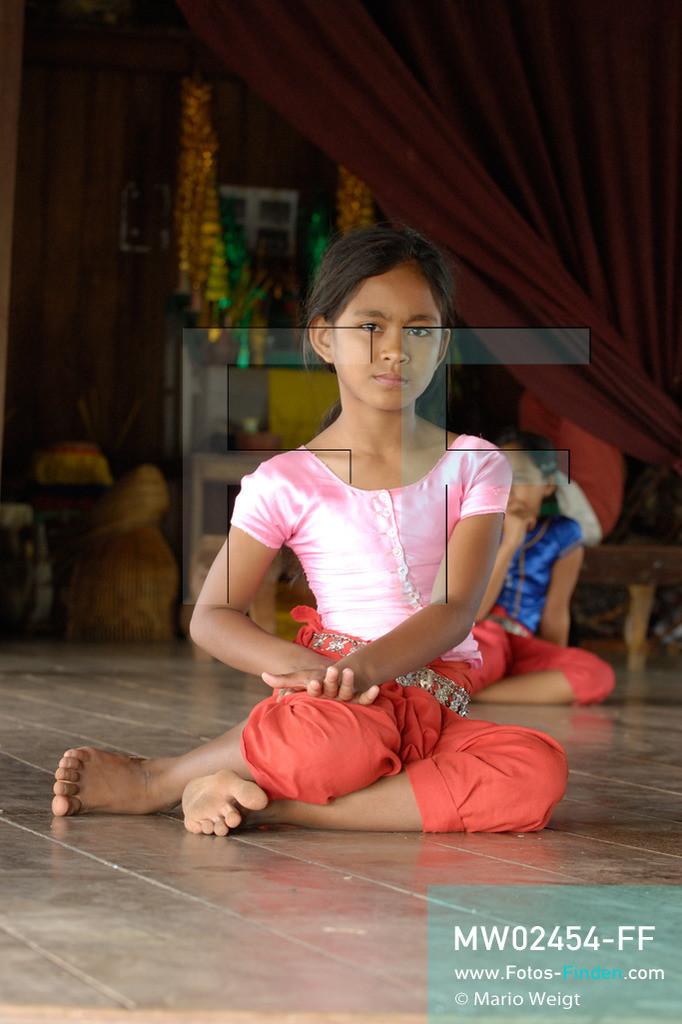 MW02454-FF | Kambodscha | Phnom Penh | Reportage: Apsara-Tanz | Für die Schülerinnen der Tanzschule beginnt jede Tanzstunde mit Aufwärmübungen. Sechs Jahre dauert es mindestens, bis der klassische Apsara-Tanz perfekt beherrscht wird. Kambodschas wichtigstes Kulturgut ist der Apsara-Tanz. Im 12. Jahrhundert gerieten schon die Gottkönige beim Tanz der Himmelsnymphen ins Schwärmen. In zahlreichen Steinreliefs wurden die Apsara-Tänzerinnen in der Tempelanlage Angkor Wat verewigt.   ** Feindaten bitte anfragen bei Mario Weigt Photography, info@asia-stories.com **