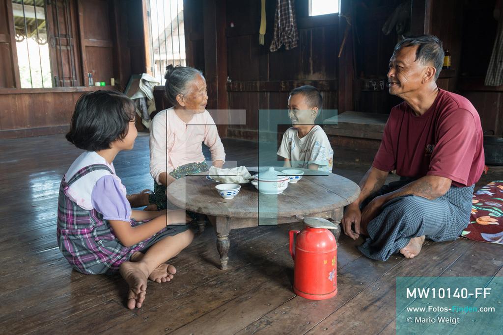 MW10140-FF | Myanmar | Inle-See | Nyaungshwe | Reportage: Ye Lin lebt auf dem Inle-See | Ye Lin trinkt mit seiner Oma Daw Khin Aye, Onkel Ko Thein Tun und Schwester Than Dar Aung Tee am Nachmittag. Der 8-jährige Ye Lin Yar Zar lebt mit seinen Eltern in einem Pfahlhaus auf dem Inle-See. Er gehört zur ethnischen Gruppe der Intha und beherrscht die einzigartige Einbeinrudertechnik, um zur Schule zukommen.  ** Feindaten bitte anfragen bei Mario Weigt Photography, info@asia-stories.com **