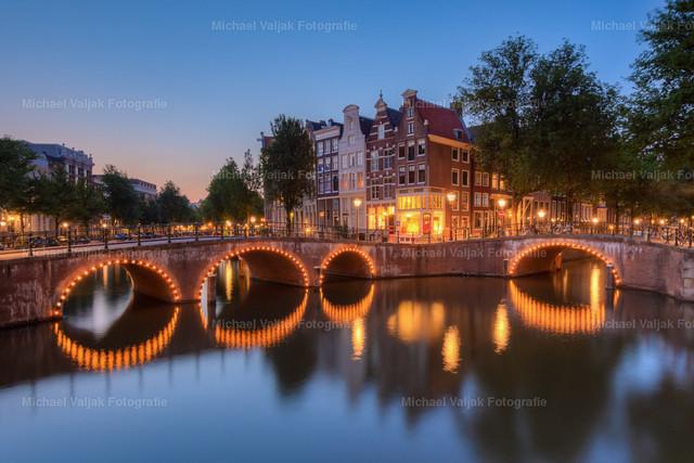Keizersgracht Amsterdam   Von den vielen Grachten in Amsterdam ist die Keizersgracht eine der schönsten. Vor allem zur blauen Stunde nach Sonnenuntergang kommen die beleuchteten Brückenbögen besonders schön zur Geltung.