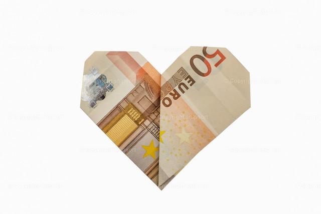 Zu einem Herz gefalteter 50-Euro-Schein | Ein aufwendig zusammengefalteter 50-Euro-Schein als Geschenk vor einem weißen Hintergrund.