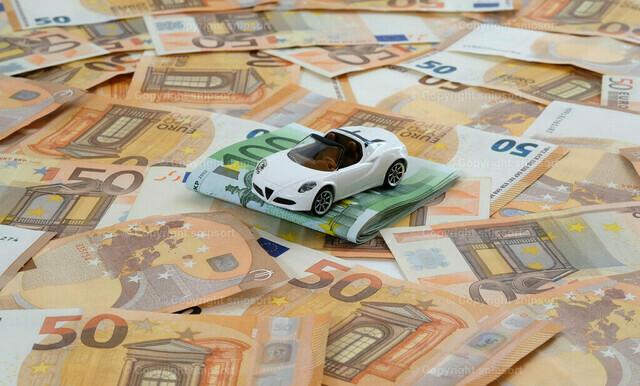 Weißes Sportauto auf einem Geldteppich | Ein Modellauto auf flächendeckend ausgelegten 50-Euro-Banknoten mit 100-Euro-Banknoten zum Thema Konzept Autokosten