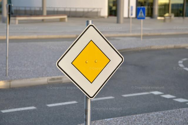 Verkehrsschild (Vorfahrtstraße) | Ein Verkehrsschild mit Straße im Hintergrund
