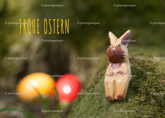 Osterkarte Oster-Eier versteckt: Frohe Ostern | ein Kantenhocker Osterhase sitzt auf einem bemoosten Stamm und hat zwei bunte Oster-Eier versteckt bei Tageslicht vor einem dunklen Hintergrund mit dem Text Frohe Ostern
