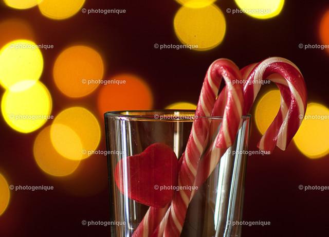 Weihnachtskarte mit drei Zuckerstangen und einem roten Herz bei Kerzenlicht | Weihnachtskarte mit drei Zuckerstangen und einem roten Herz bei Kerzenlicht
