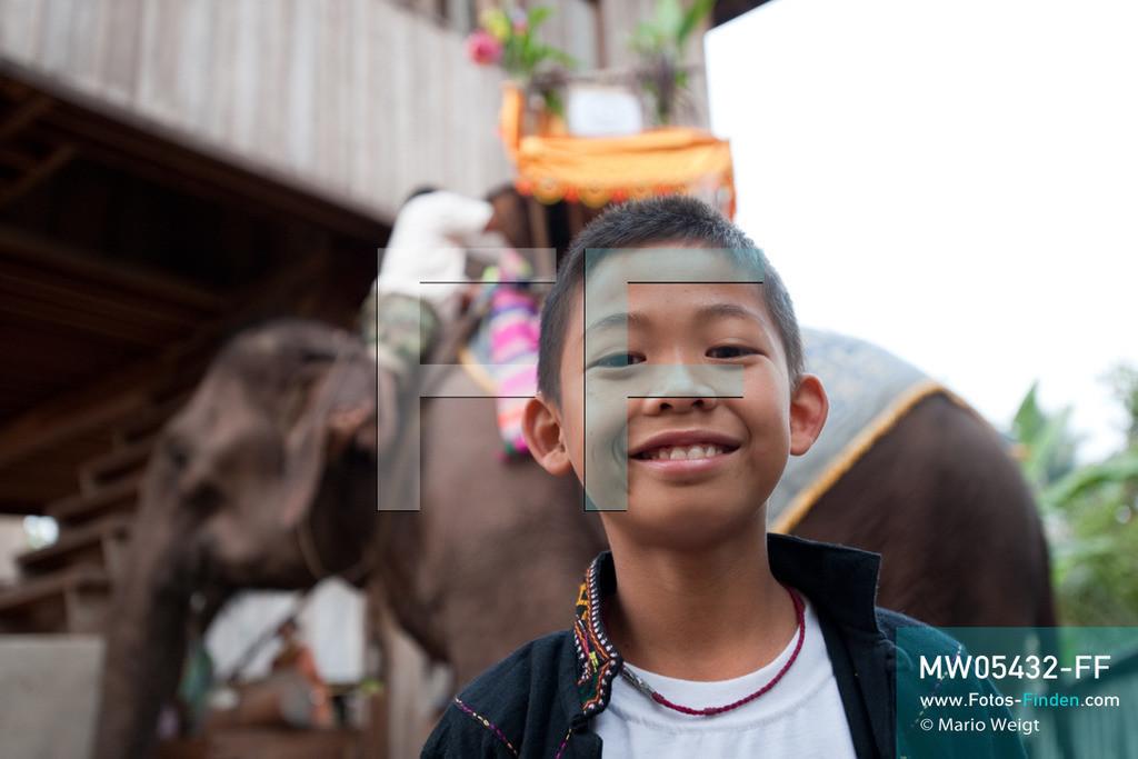 MW05432-FF | Laos | Provinz Sayaboury | Vieng Keo | Reportage: Pey Wan im Elefantendorf | Porträt von Pey Wan vor seinem Wohnhaus.  Der achtjährige Pey Wan lebt im Elefantendorf Vieng Keo im Nordwesten von Laos. Im Dorf wohnen ca. 500 Leute mit 17 Arbeitselefanten. Sein Vater Hom Peng hat einen 31 Jahre alten Elefantenbullen namens Boun Van, mit dem er im Holzfällercamp im Dschungel arbeitet. Zum Elefantenfest schmückt Pey Wan den Jumbo und darf mit ihm an der Prozession durchs Dorf teilnehmen. Pey Wan möchte, wie sein Vater, später auch Elefantenführer werden.   ** Feindaten bitte anfragen bei Mario Weigt Photography, info@asia-stories.com **