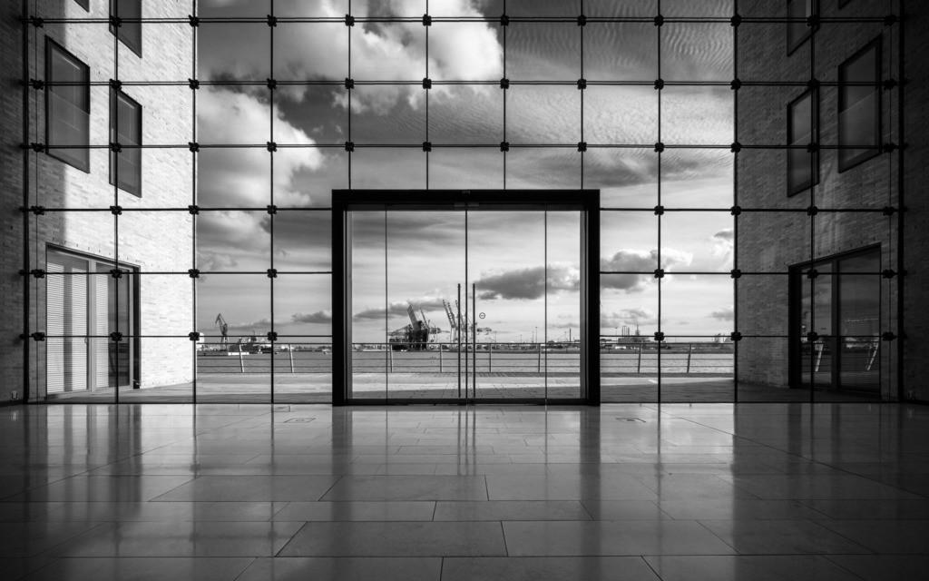 The View Mono   Die Fensterfront der Lobby eines Bürogebäudes im Hamburger Hafen