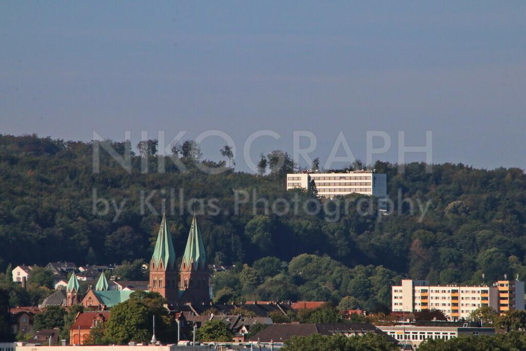 Iserlohner Panorama | Panoramablick über Iserlohn. Die markanten Kirchtürme der Aloysiuskirche ragen über die Stadt. Die Fachhochschule Iserlohn ist im Stadtwald eingebettet.
