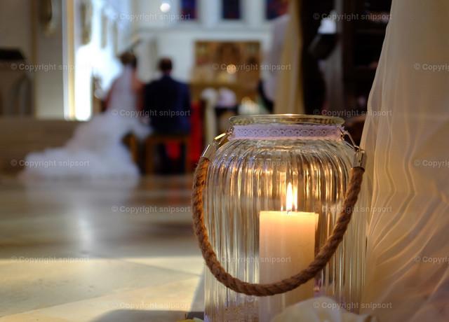 Trauung in der Kirche | Detail von einer Kerze mit einem sich trauunden Paar im Hintergrund.