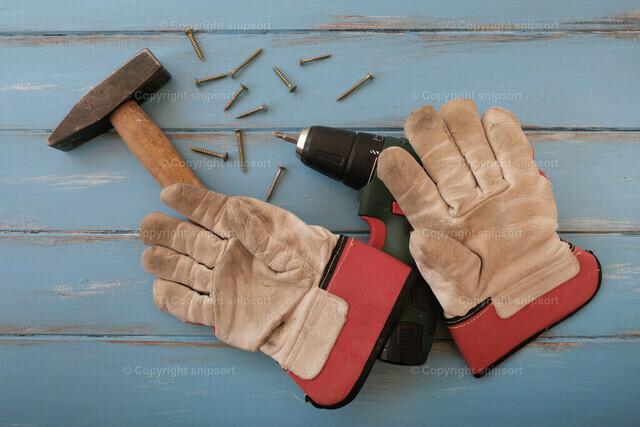 Handwerkerwerkzeug | Arbeitshandschuhe, Hammer, Akkuschrauber als Konzept für Handwerk und Hobby.