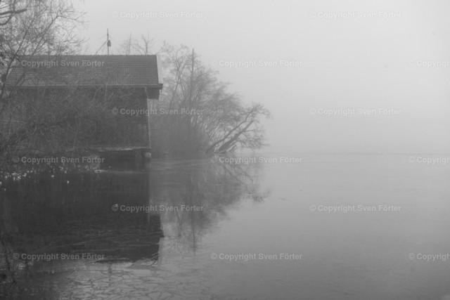 Bootssteg im Nebel | schwarz-weiß Bild eines Bootshauses im Nebel am Pelhamer See in Bad Endorf