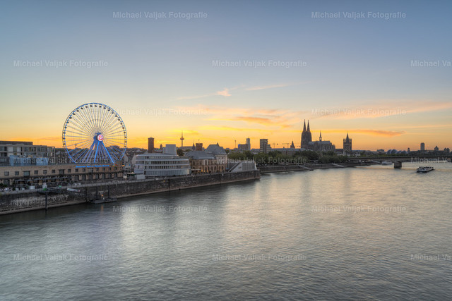Kölner Skyline mit Riesenrad bei Sonnenuntergang | Blick von der Severinsbrücke in Richtung Rheinauhafen mit Riesenrad neben dem Schokoladenmuseum und der Altstadt mit dem Kölner Dom im Hintergrund.
