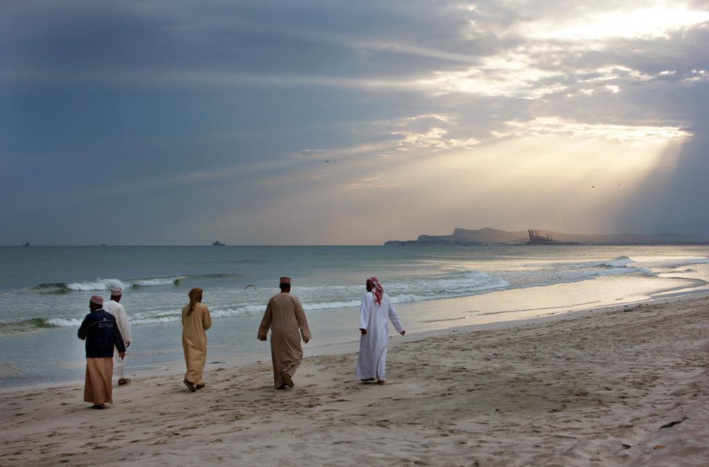 JT-090122-064 | Oman, Salala, Männer machen einen Strandspaziergang am Abend,