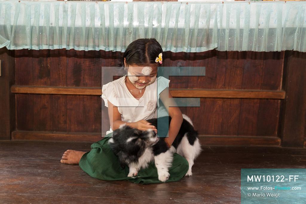 MW10122-FF | Myanmar | Hpa-an | Reportage: Zin mag Thanaka-Paste | Zuhause spielt Zin gern mit Hund Kaea Kaea. Die 7-jährige Nwe Zin Aye lebt im Dorf La Ka Nha nahe der Stadt Hpa-an. Sie bemalt gern ihr Gesicht mit Thanaka-Paste. Nach der burmesischen Tradtition tragen fast alle Mädchen und Frauen diese Art von Schminke.   ** Feindaten bitte anfragen bei Mario Weigt Photography, info@asia-stories.com **