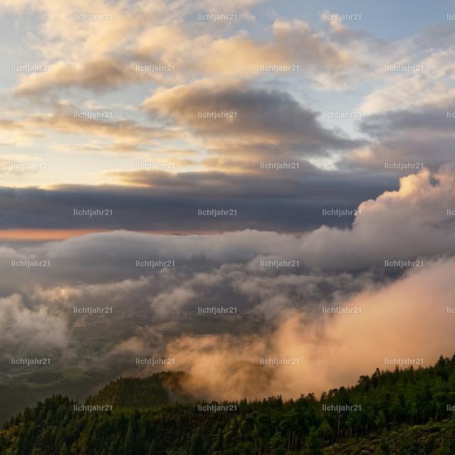 Das Licht der Azoren | Die untergehende Sonne färbt markante und kontrastreiche Wolkenformationen, die in verschiedenen Schichten und Höhen vor und über der steil ansteigenden Landschaft hängen - Location: Azoren, Sao Miguel, Gebiet