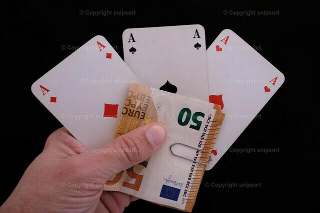 Drei Asse in der Hand mit dem Spieleinsatz   Drei Asse in der Hand mit den Fünfzigerscheinen als Einsatz vor schwarzem Hintergrund.