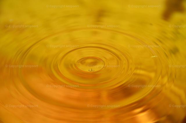 Wassertropfen mit konzentrischen Wellen | Konzentrische Welle auf der Wasseroberfläche (Detail einer gelb schimmernden Flüssigkeit).
