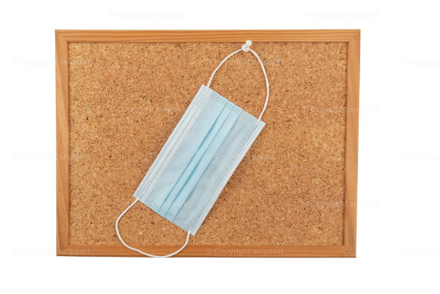 Auf einem Pinnbrett befestigte Mundschutzmaske | Konzept für Erinnerung, eine Mundschutzmaske mitzunehmen