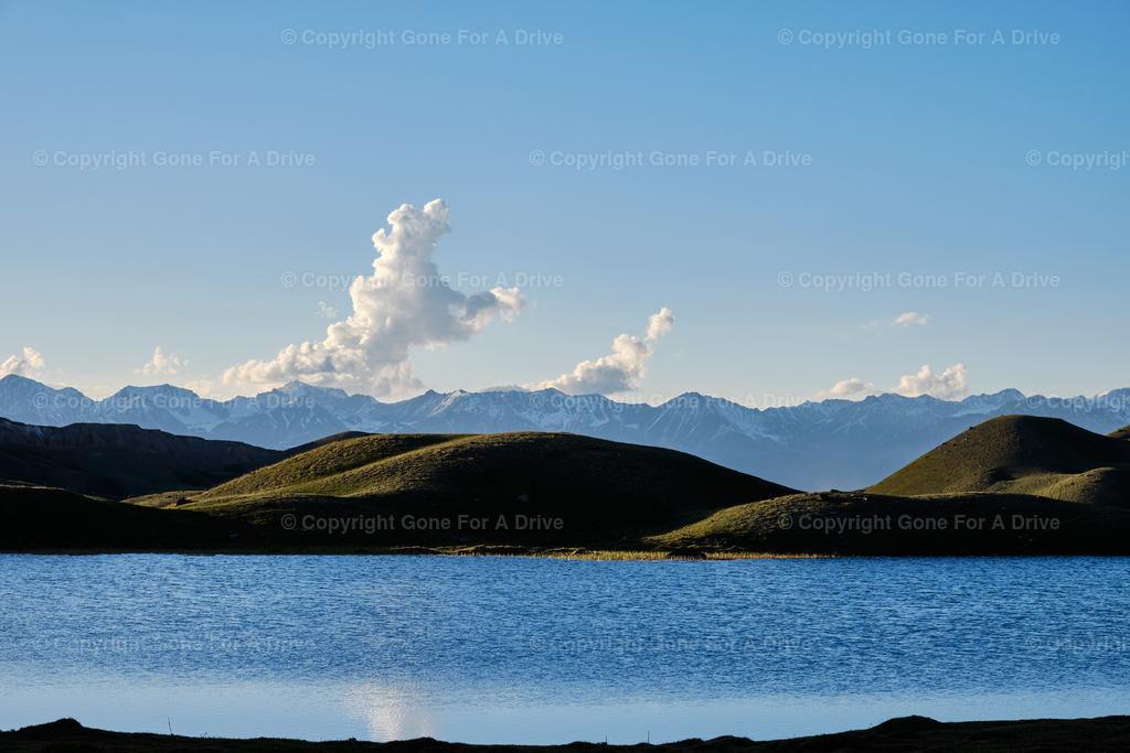 Kirgistan | Ein kleiner See, grüne Hügel im Sonnenuntergangslicht und schroffe Bergspitzen im Hintergrund.