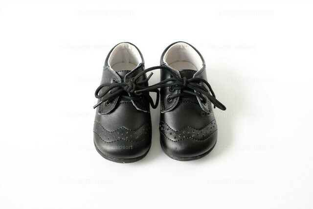 Kinderschuhe | Ein paar schwarze Kinderschuhe für Jungen über weißem Hintergrund.