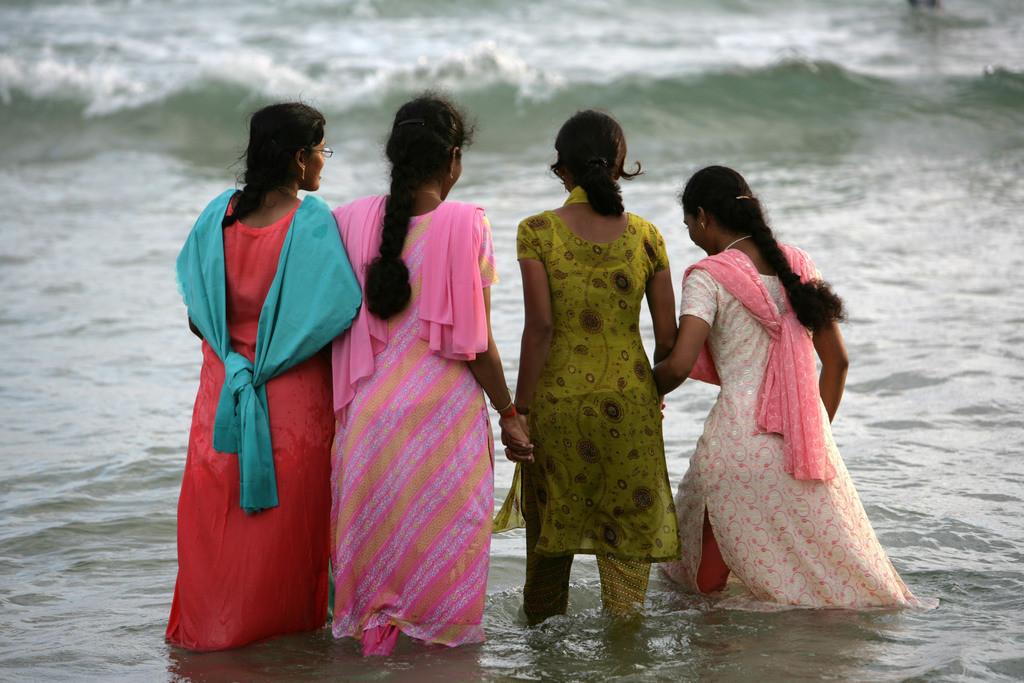 Indien, Kerala | Indien, Kerala, Trivandrum, Kovalam Beach, Lighthouse Beach, junge Frauen gehen im seichten Wasser am Strand, in ihren Saris, baden.