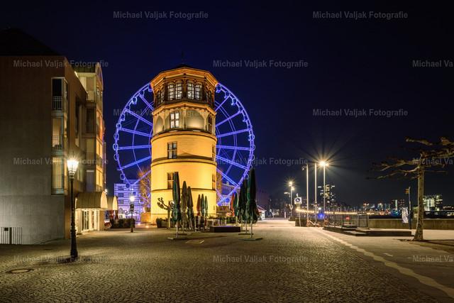 Schlossturm und blaues Riesenrad in Düsseldorf | Blau beleuchtetes Riesenrad auf dem Burgplatz in der Düsseldorfer Altstadt, mit dem Schlossturm im Vordergrund.
