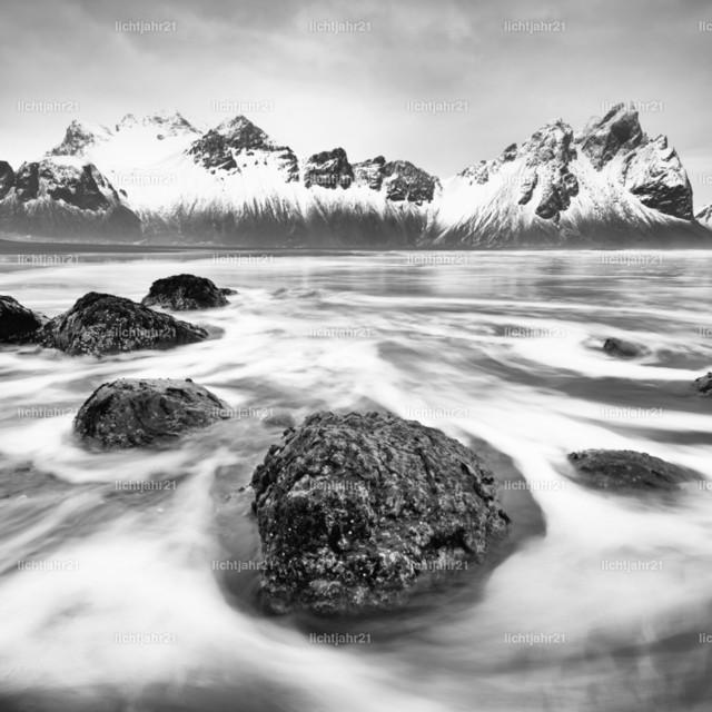 Bergkette vor wilder Brandung | Schwarzweißbild einer schneebedeckten Bergformation, die sich im Wasser eines schwarzen Lavasandstrandes spiegelt, im Vordergrund von Wellen umspülte Steine, große Tiefenwirkung - Location: Island, Südküste