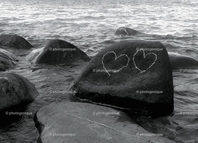 zwei Herzen auf Felsen   zwei Herzen mit Kreide auf Findling im Wasser gemalt