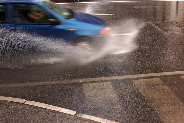 Auto fährt in die Pfütze | Vorbeifahrendes Auto fährt in eine tiefe Pfütze