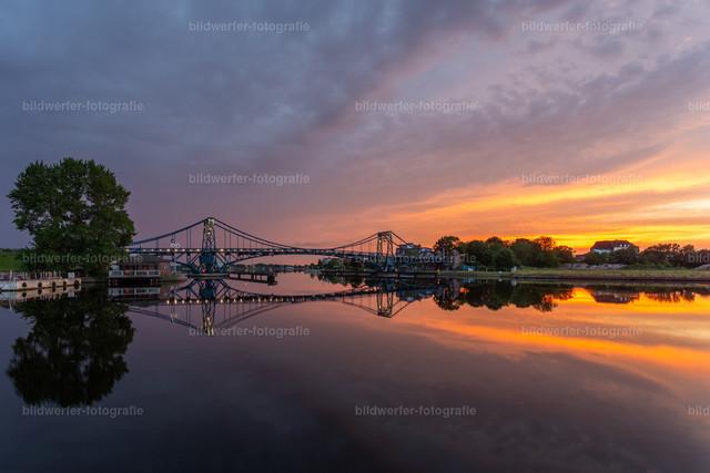 Kaiser-Wilhelm-Brücke mit dramatischem Himmel   Kaiser-Wilhelm-Brücke im Sonnenuntergang kurz vor einem Gewitter und Spiegelung im Wasser