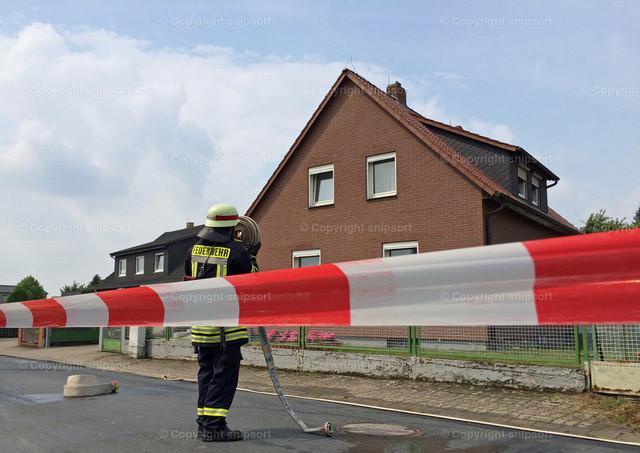 Feuerwehr im Einsatz | Feuerwehrmann beim Abrollen des Schlauchs hinter dem weißroten Absperrband.