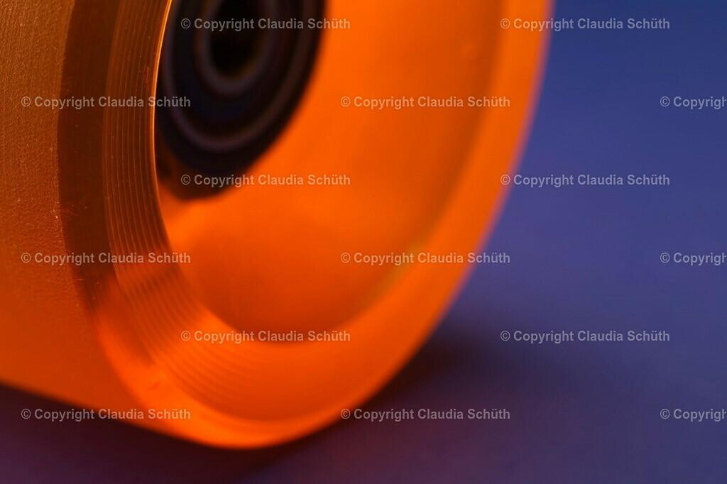 Eine Longboard-Rolle mit Kugellager in Orange   Eine Longboard-Rolle mit Kugellager in Orange auf blauem Untergrund.