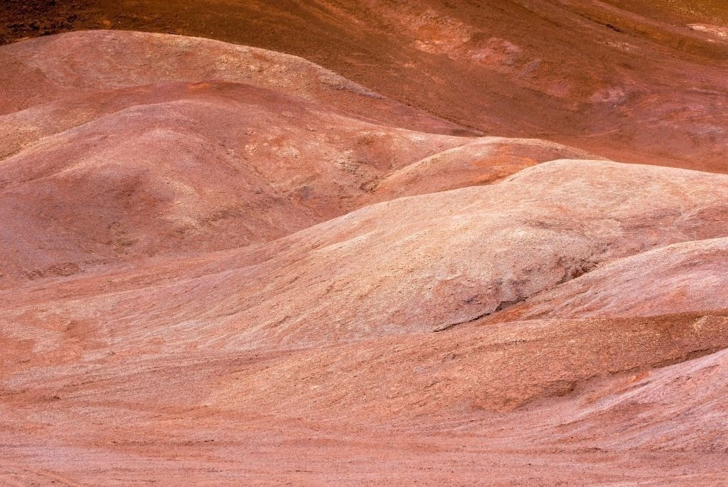Best. Nr. erde14 | Geschwungene Formen roter Erde im Waimea Canyon, Hawai'i, USA  | Das Element Erde repräsentiert das Zentrum aber auch den Südwesten und Nordosten, seine Jahreszeit ist der Spätsommer, seine Farben sind Gelb und braune und beige Naturtöne, es bieten sich quadratische oder flache rechteckige Formate und horizontale Formen an. Erde steht für Bodenständigkeit, Dauerhaftigkeit und Zuverlässigkeit. Geeignet sind solche Bilder z.B. für Wohnzimmer oder Räume, in denen man sich zentrieren und abschalten möchte.